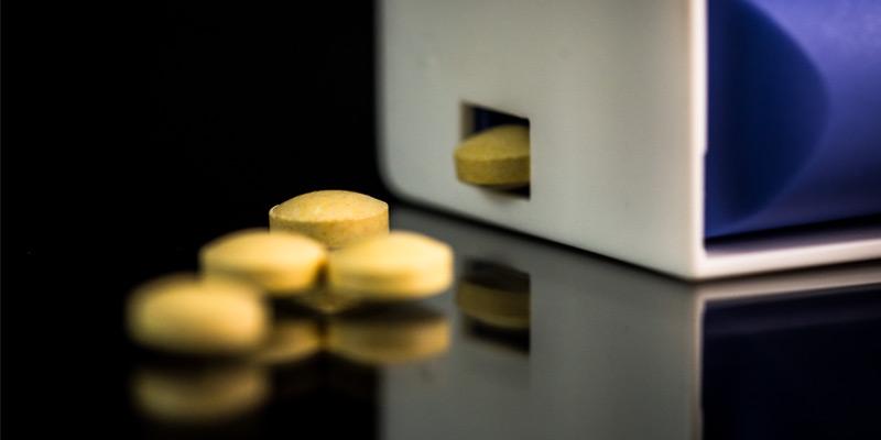 Folsäure Tabletten und Spender auf einer schwarzen, reflektierenden Oberfläche